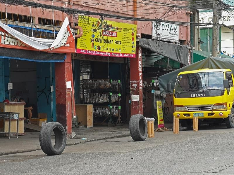 DAVAO. Tires and other items are placed by several business establishments in the road to prevent other vehicles from parking in front of their establishments, making the road exclusive for them. (SunStar Davao)