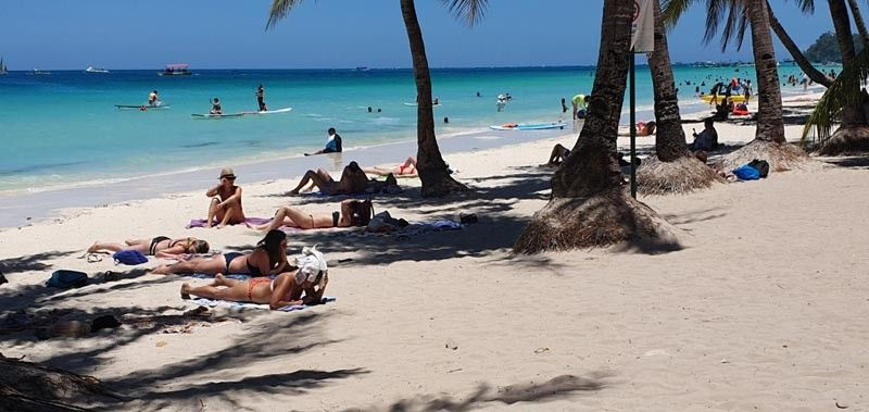 BORACAY. Tourists frolicking in the white sand beach of Boracay Island. Tourists who have night flights are urged to check out early due to limited sea travel imposed by the government. (Photo by Jun N. Aguirre)