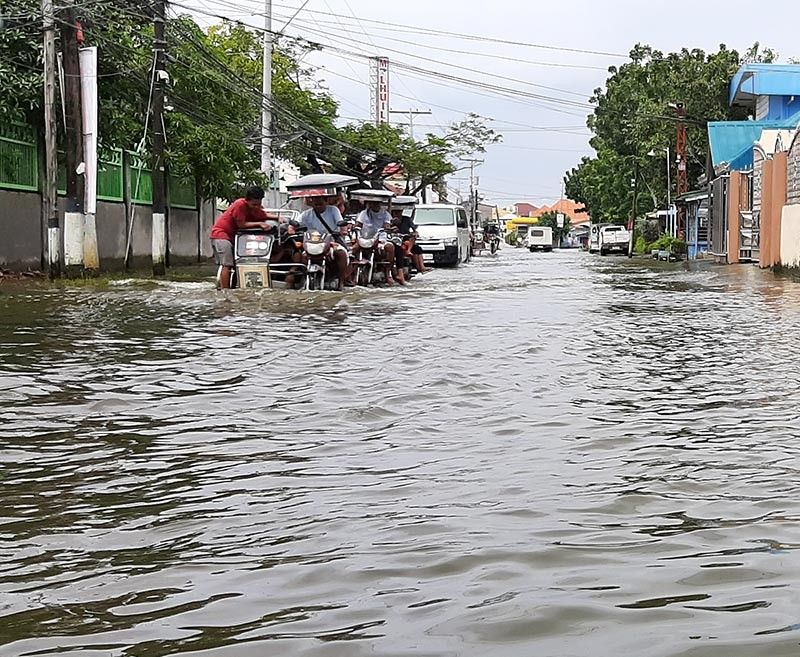 PAMPANGA. Motorists brave the almost knee-deep floodwaters in Barangay Caduang Tete, Macabebe to go to and from the town proper. (Photo by Princess Clea Arcellaz)