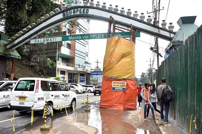 BAGUIO. Pedestrians and motorists pass at their own risk under the temporary post that provides support to the welcome arch near the BGH Rotunda after it was damaged by continues rains brought by the Southwest monsoon in the past weeks. (Photo by Redjie Melvic Cawis)