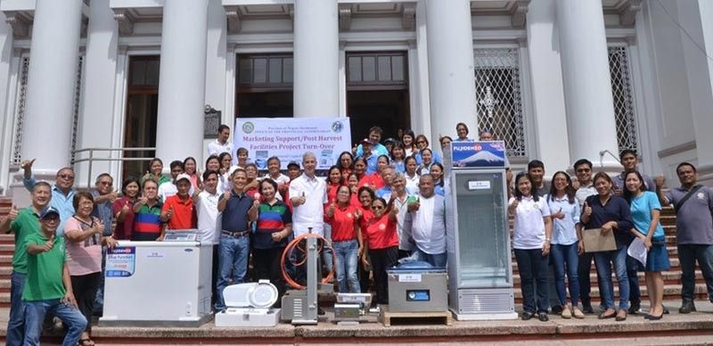 BACOLOD. Governor Eugenio Jose Lacson (ninth from left) with Third District Board Member Andrew Montelibano (sixth from left), Provincial Veterinarian Renante Decena (seventh from left), Hinoba-an mayor Ernesto Estrao (left) and recipients of P5 million worth of post-harvest facilities during the turnover ceremony at the Provincial Capitol Grounds in Bacolod City Wednesday, September 4, 2019. (Photo by Richard Malihan)