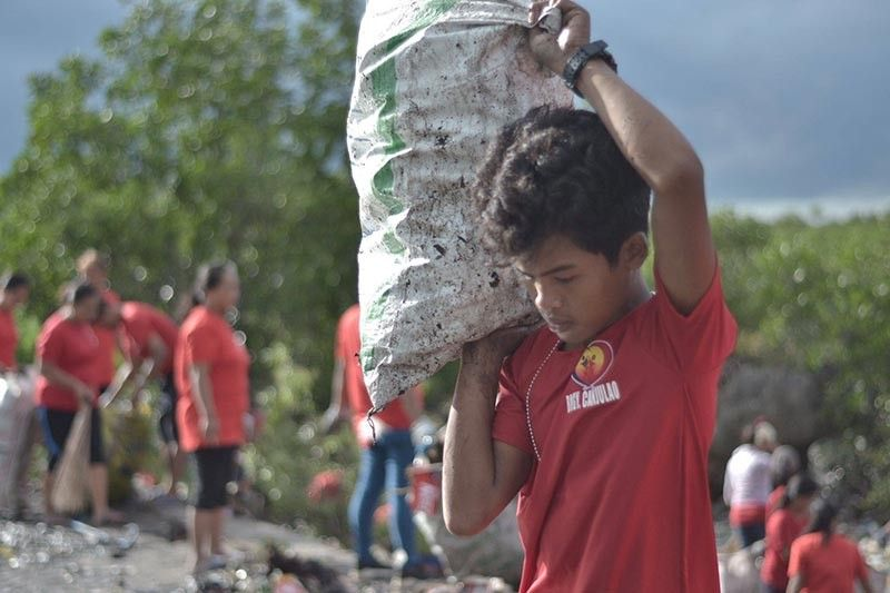 CIVIC DUTY. A young man joins some 300 volunteers during a coastal cleanup in Barangay Canjulao,  Lapu-Lapu City. The group collected around eight tons of garbage on Sept. 3, 2019. (Contributed Photo / Ariel Berdon)