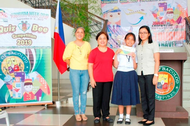 Loren Andrea Bertuso (2nd from right), a Grade 6 pupil of Luis B. Puentevella Elementary School, was declared champion in the Quiz Bee elementary level during the Tourism Week of Bacolod City. Also in photo (from left) Quiz Bee moderator Filomena Lo, Acting City Tourism Officer Sandra Ruth Sycip, and Bertuso's coach Nemi Macayan. (Contributed photo)