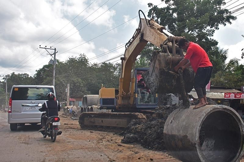 ROAD WORKS. A worker detaches a metal after extracting a culvert during the ongoing drainage improvement in Indangan, Davao City. (Macky Lim)