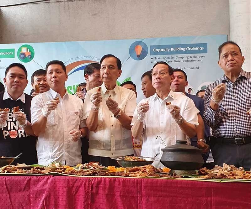 MANILA. Agriculture Secretary William Dar, center, participate in a boodle fight with private and commercial hog raisers to show that pork and pork-based products are safe to eat. (Photo from William Dar Facebook)