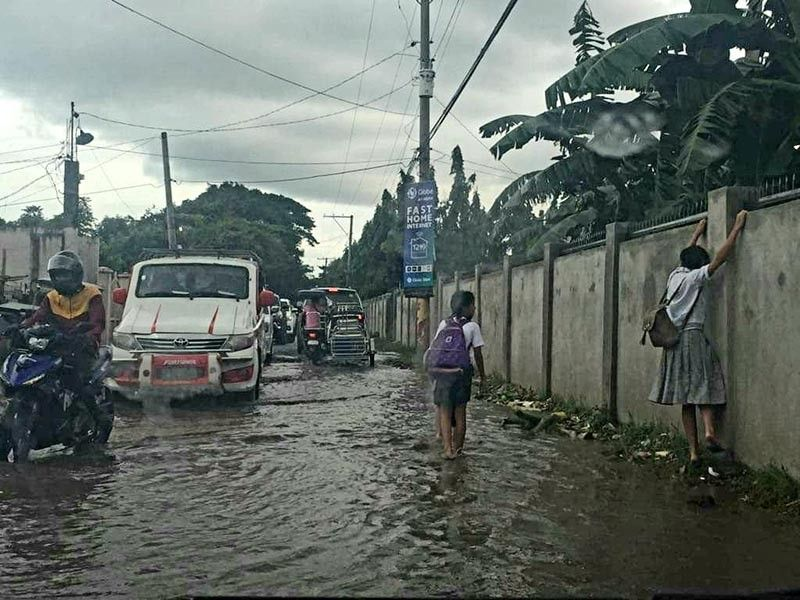 PAMPANGA. A student in San Simon town tries to avoid being dipped in stagnant floodwaters while on her way to school. (Princess Clea Arcellaz)