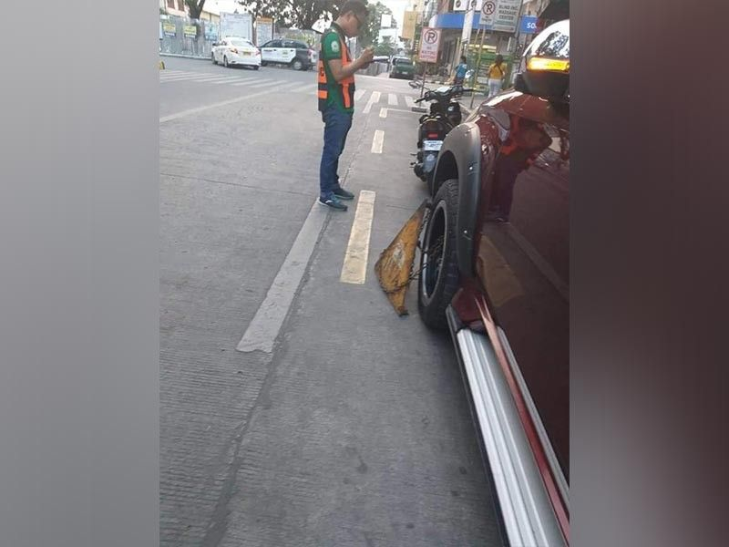 CAGAYAN DE ORO. A personnel of the Roads and Traffic Administration (RTA) clamps a Mitsubishi Montero and issues citation for illegal parking. The RTA is looking for the driver of the Montero vehicle after the clamp attached to it was found damaged by traffic personnel. (Photo by RTA)