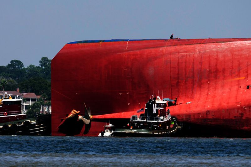 GEORGIA. Rescuers work near the stern of the vessel Golden Ray as it lays on its side near the Moran tug boat Dorothy Moran, Monday, September 9, 2019, in Jekyll Island, Georgia. Coast Guard rescuers have made contact with four South Korean crew members trapped inside the massive cargo ship off the coast of Georgia. (AP)