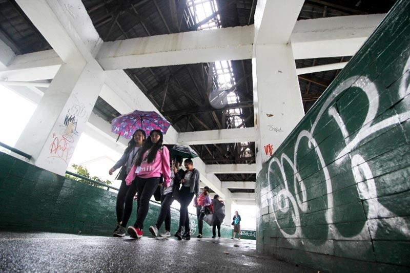 BAGUIO. Pedestrians use their umbrellas when traversing the overpass near the Baguio City National High School due to its dilapidated state. Aside from unrepaired roof, the area is also vandalized. (Photo by Jean Nicole Cortes)