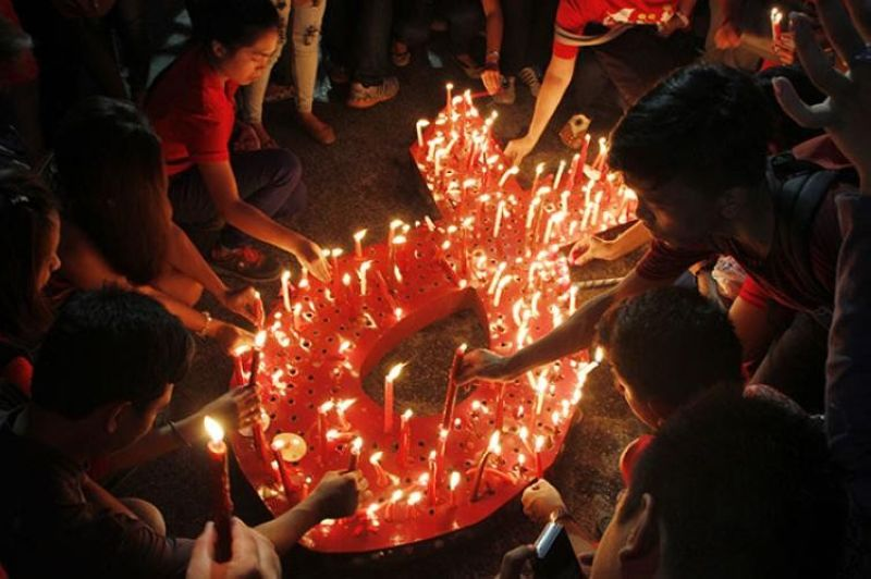 In this file photo, protesters light candles to protest the discrimination against people living with HIV. (File Photo)