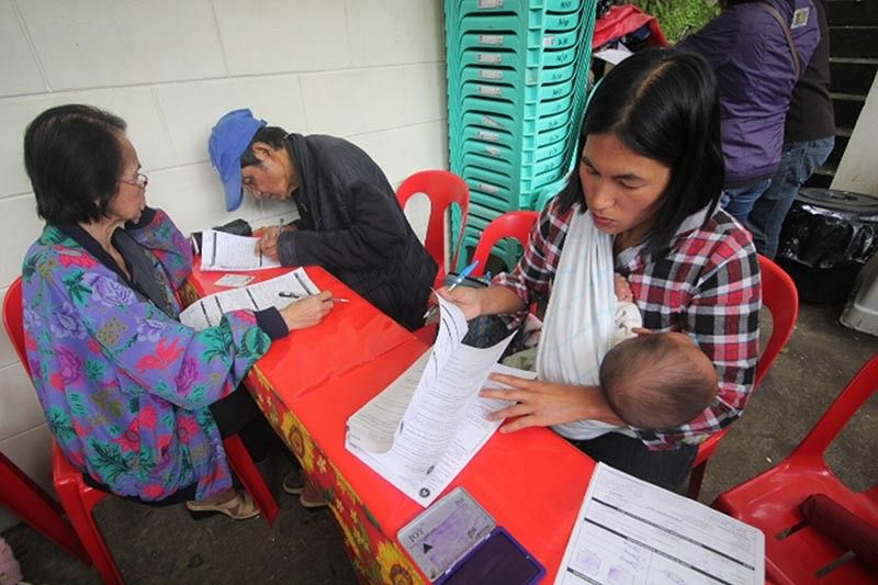 BAGUIO. With a baby in tow, a mother fills-up necessary information at the Commission on Elections (Comelec) Baguio for the voter's registration for the 2020 barangay elections. Voter's registration started on August 1 and will run until September 30. (Photo by Jean Nicole Cortes)