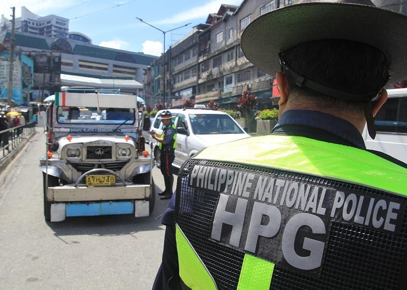 BENGUET. Highway Patrol Group (HPG) officers cite a jeepney driver defying the no loading and unloading sign along Upper Magsaysay Avenue. While authorities strictly implement traffic rules to decongest the city, jeepney drivers plea for a designated loading and unloading zone along the area. (Photo by Jean Nicole Cortes)