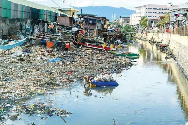 SHRINKING RIVER. In this file photo the Guadalupe River exits through Barangays Pasil (left) and Ermita in Cebu City, much narrowed by the encroachment of houses and trash on its banks. Is it any wonder that when heavy rains come, the river overflows? (Arni Aclao)