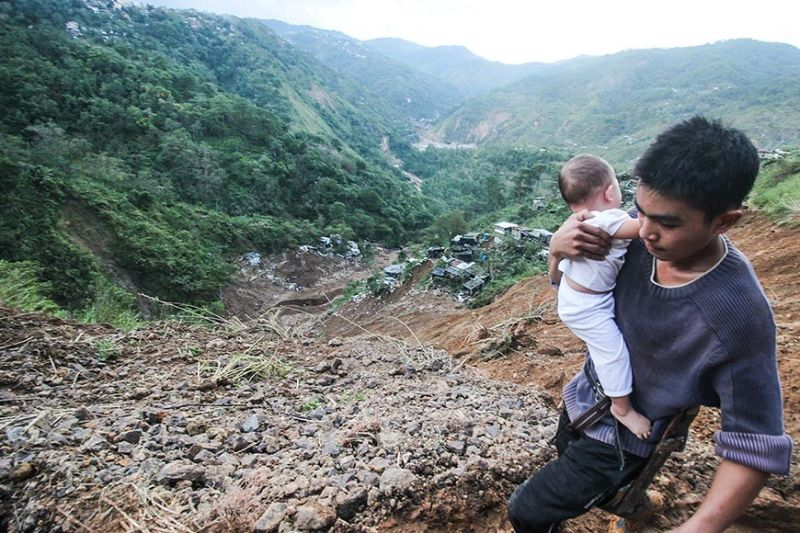 BENGUET. In this photo taken September 2018, a resident of Itogon bravely crosses the landslide-stricken area just above Sitio 070, Barangay Ucab in Itogon, Benguet to evacuate. (Jean Nicole Cortes)
