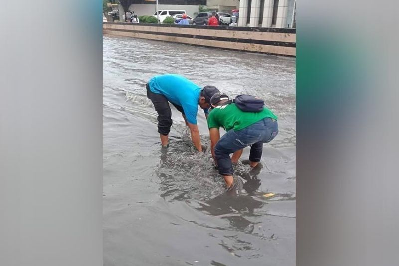 HIGHWAY OF FLOOD. Two men clear a drainage from garbage along the Natalio B. Bacalso South National Highway in Talisay City, Cebu during a downpour on Tuesday afternoon, Aug. 20, 2019. (Contributed photo)