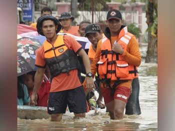 ZAMBOANGA. Philippine Coast Guard personnel assist in the evacuation of flood-displaced families as Tropical Depression Marilyn inundates 11 villages in Zamboanga City. (Photo by Bong Garcia)