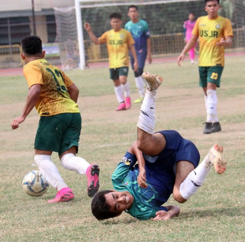 HEAD OVER HEELS. A player from the University of San Carlos loses his footing as he goes for a challenge against the University of San Jose-Recoletos. (SUNSTAR FOTO / AMPER CAMPAÑA)