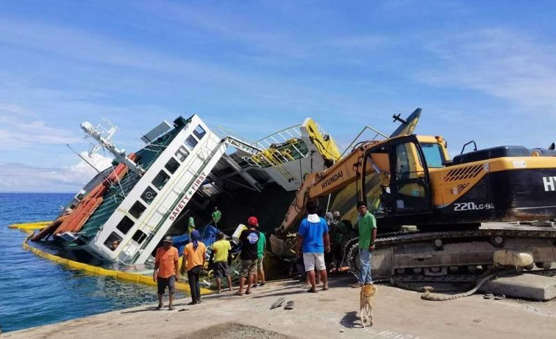 CEBU. Workers use a backhoe to retrieve mv Mika Mari 8 on Sunday morning, September 1, 2019. The ship titled on its side while it was unloading cargo and passengers in the port of Barangay Consuelo, San Francisco, Camotes Island last Aug. 31. (Contributed photo/Arianne Capao)