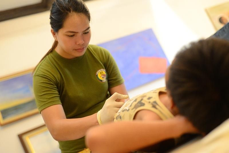 ILOILO. A civilian volunteer of the 61th Infantry Battalion performs a circumcision to a 12-year-old boy at Sulu Garden in Miagao, Iloilo during a medical-dental mission Sunday, September 15, 2019. (Leo Solinap)