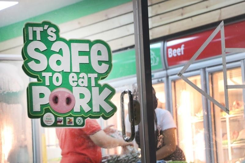 "PAMPANGA. Amid the threat of African swine fever and the ban on the entry of live hogs in Pampanga, a meat shop posted on its door that ""it's safe to eat pork"". (Photo by Chris Navarro)"