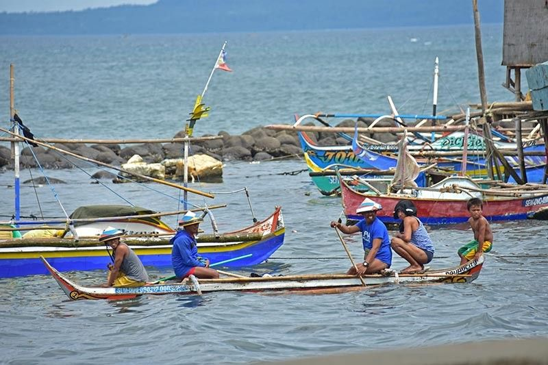 DAVAO. A group of fishermen rides a small boat as they head to their fishing boat docked few meters away from the seawall in Barangay 23-C Isla Verde, Davao City. (Macky Lim)