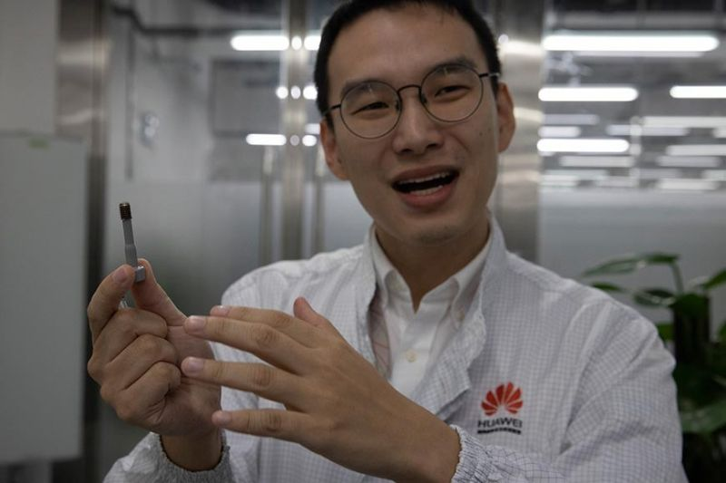 CHINA. In this August 21, 2019, photo, a Huawei research engineer holds up a coated screw designed to reduce signal interference at the Huawei Materials lab in Dongguan in Southern China's Guangdong province. Facing a ban on access to U.S. technology, Chinese telecom equipment maker Huawei is showing it increasingly can do without American components and compete with Western industry leaders in pioneering research. (AP)