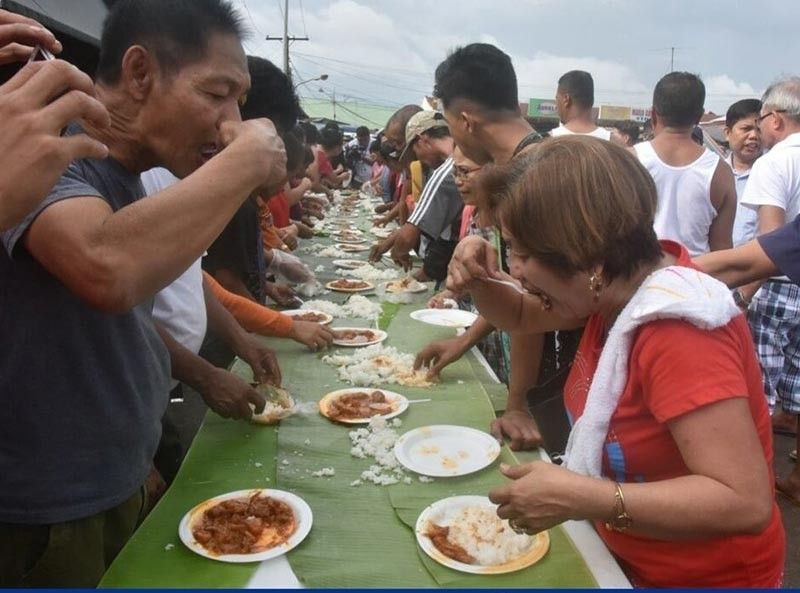 PAMPANGA. Guagua meat vendors do a boodle fight of different pork dishes at the Guagua Public Market to show pork products sold there are safe. (Pampanga PIO)