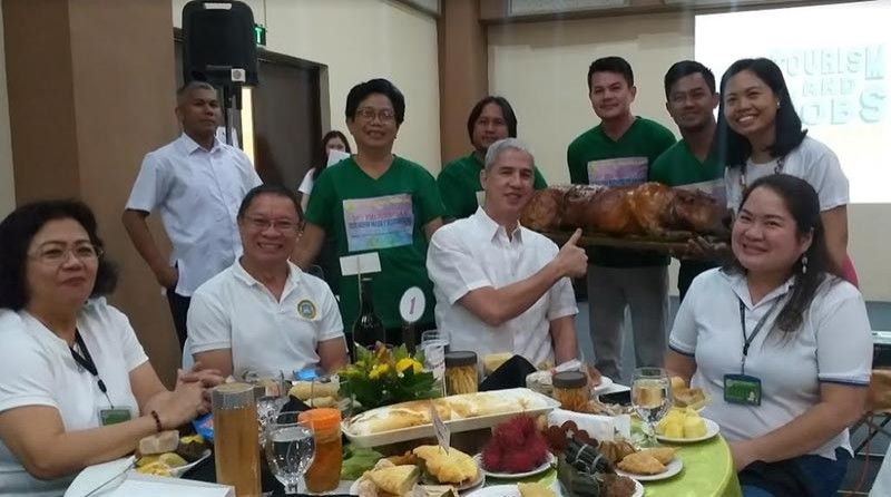 BACOLOD. Provincial government officials led by Governor Eugenio Jose Lacson (seated, second from right) and Provincial Supervising Tourism Operations Officer Cristine Mansinares (standing right) during the food parade, one of the activities at the ongoing 19th Provincial Tourism Week celebration in Negros Occidental. (Photo by Erwin P. Nicavera)