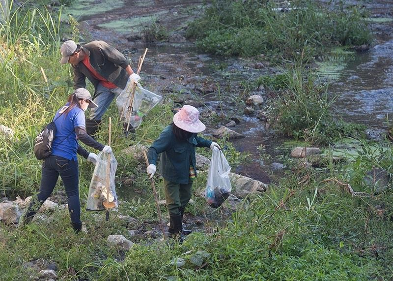 BENGUET. Volunteers work together to gather trash from the polluted Balili River drive in a bid to clean and save our inland waterways. Another clean-up drive will take place on September 20 at Agno-Ambalango, Asin-Galiano, Balili and Bued Rivers. (Photo by Jean Nicole Cortes)