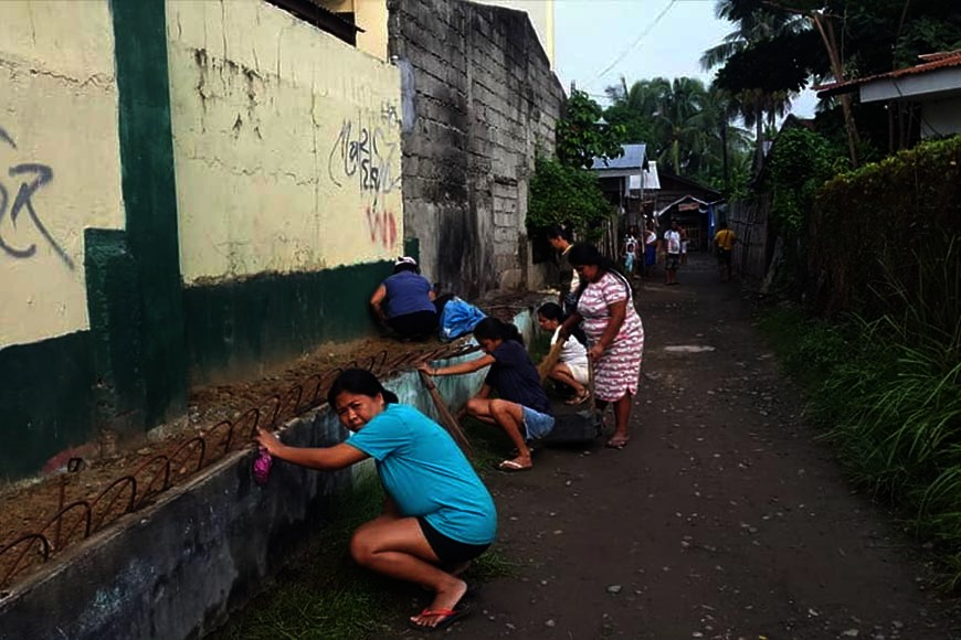 CAGAYAN DE ORO. Some less fortunate residents under the government's  4Ps program render community service by cleaning up the driveway of Bonbon Elementary School one morning in Cagayan de Oro City. (Lynde Salgados)