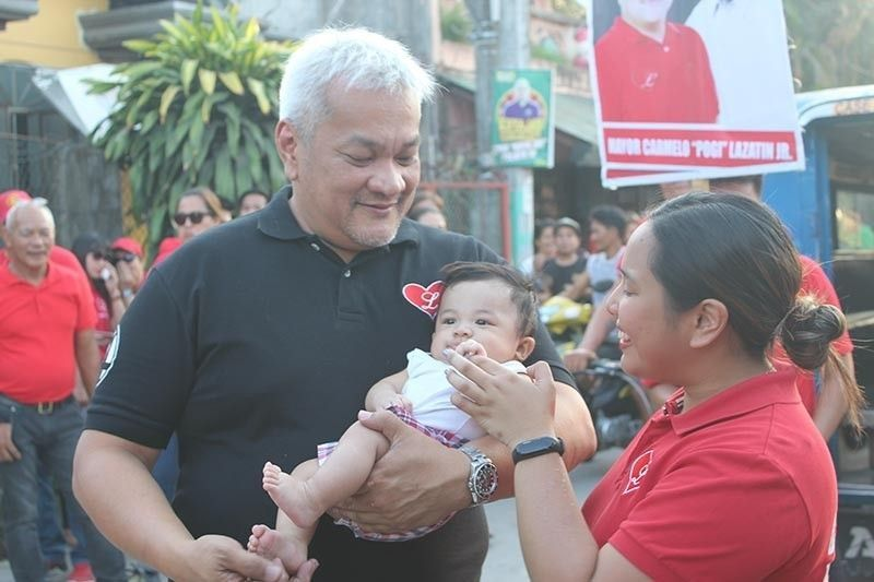 "PAMPANGA. Mayor Carmelo ""Pogi"" Lazatin, Jr. cuddles a child during one of his rounds of the city promoting an immunized, healthy community. (Chris Navarro)"