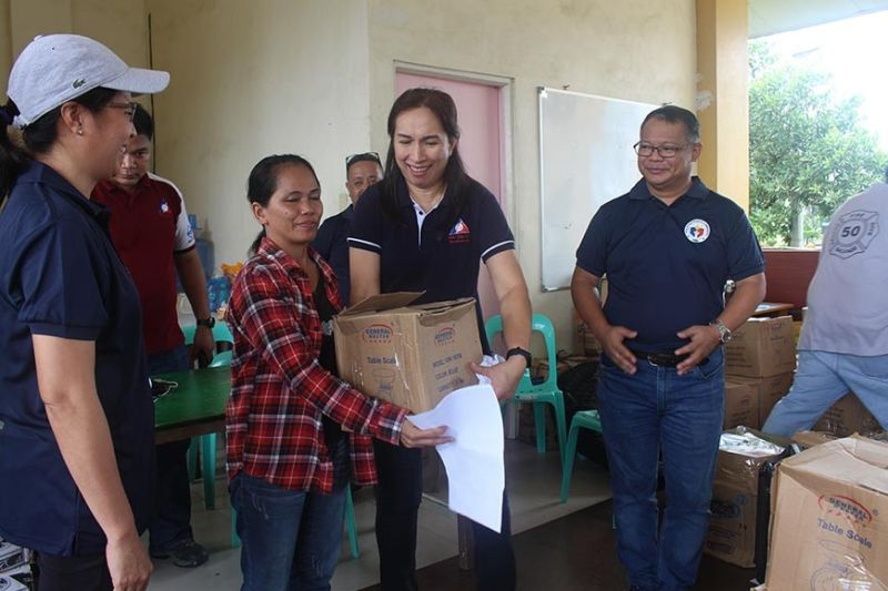 PAMPANGA. Department of Labor and Employment regional director Zenaida Angara-Campita hands over livelihood assistance to a Hanjin worker on September 19 during the turnover of P2.125 million worth of livelihood package at Hanjin Village, Castillejos, Zambales. (Contributed photo)