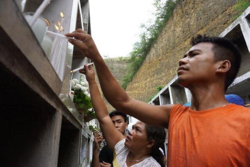 HUGKAS: Mga kabanay sa mga nangamatay sa landslide sa Dakbayan sa Naga nanagkot sa mga lubong sa ilang mga mahal sa kinabuhi tangkod og usa ka tuig human sa trahedya. (Alex Badayos)