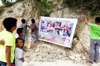 "AS IF THIS LESSON WASN'T PAINFUL ENOUGH: The Campanilla family hangs a tarpaulin at Ground Zero in Sitio Sindulan, Brgy. Tina-an, City of Naga, Cebu to remember the 16 family members they lost in the Sept. 20, 2018 landslide. A year later, more than 400 families are back in Naga's ""no habitation"" zones. (Photo by Alex Badayos)"