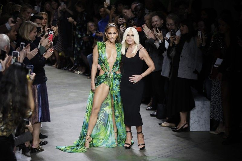 ITALY. Actress Jennifer Lopez, left, and designer Donatella Versace accept applause at the conclusion of the Versace Spring-Summer 2020 collection, unveiled during the fashion week, in Milan, Italy, Friday, September 20, 2019. (AP)