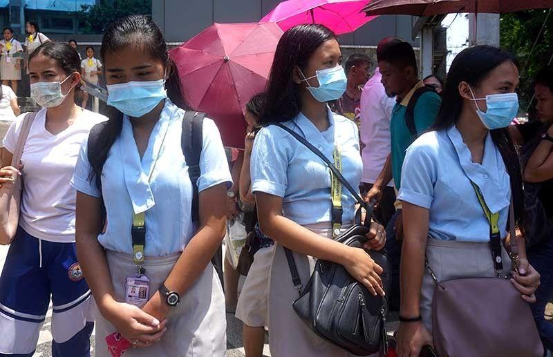 FACE MASK: Pipila sa mga tinun-an sa Sugbo ang naggamit og face mask human sa nasinate ang gabo o haze. (Alex Badayos)