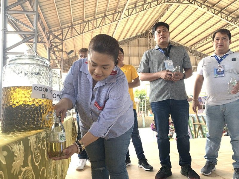 PAMPANGA. Lubao Mayor Esmeralda Pineda refills a bottle with cooking oil to officially open the 1st Lubao Refill Revolution in Prado Siongco, Lubao, Pampanga where residents from various barangays bought consumer products like cooking oil, detergent powder, and condiments at low prices (Photo courtesy of Albert B. Lacanlale)