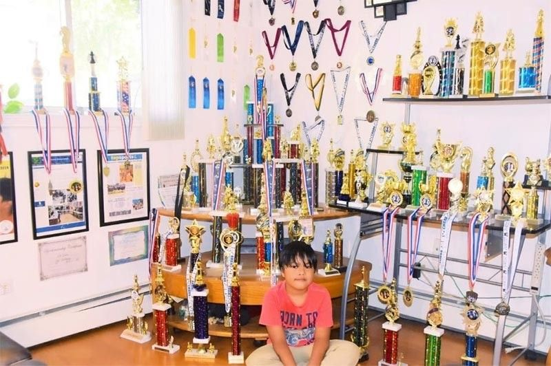 Scott Matthew Escalera poses around his trophies and medals. (Contributed Photo)