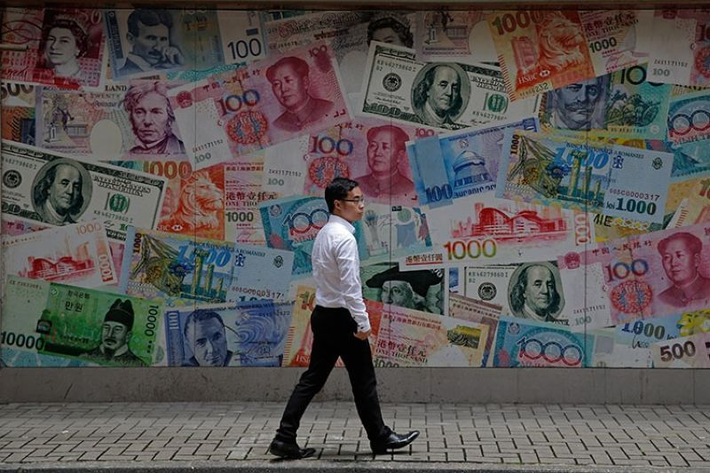 HONG KONG. In this June 10, 2019, file photo, a man walks past a money exchange shop decorated with different banknotes at Central, a business district of Hong Kong. (AP)