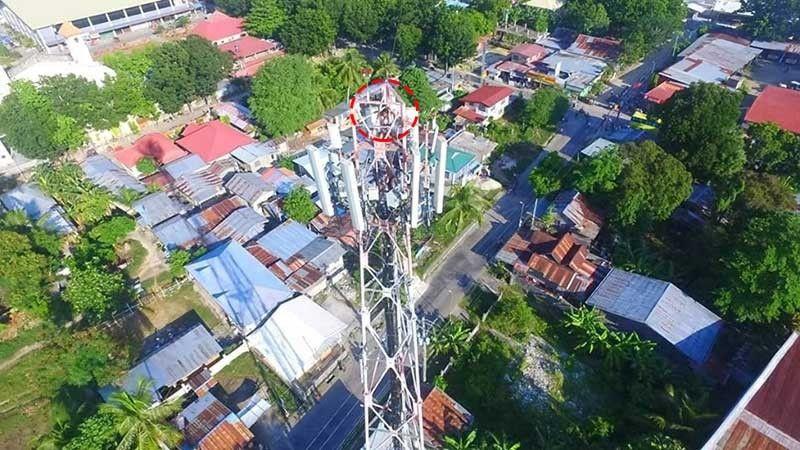 HAAAY GUGMA: Naa sa tumoy aning cellular tower sa Barangay Poblacion, Medellin, amihanang Sugbo, ang 17 anyos nga dalaga (gilinginan),  kinsa misaka alas 6:45 sa buntag sa Biyernes, Septiyembre 27 human gikalalis ang maguwang niining babaye labot sa uyab niini. Ang tower dunay gitas-ong mga 50-80 metros. (Tampo ni Rhajeev Torres)