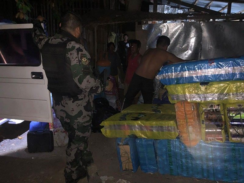 BIG HAUL.Policemen secure some 2,900 butane canisters outside a warehouse in Barangay Mactan, Lapu-Lapu City, 192 of which were refilled illegally. Refilling butane canisters with liquefied petroleum gas is unsafe and illegal, and violates Batas Pambansa 33, which penalizes the selling and distribution of certain petroleum products. (SunStar Photo/LLCPO)
