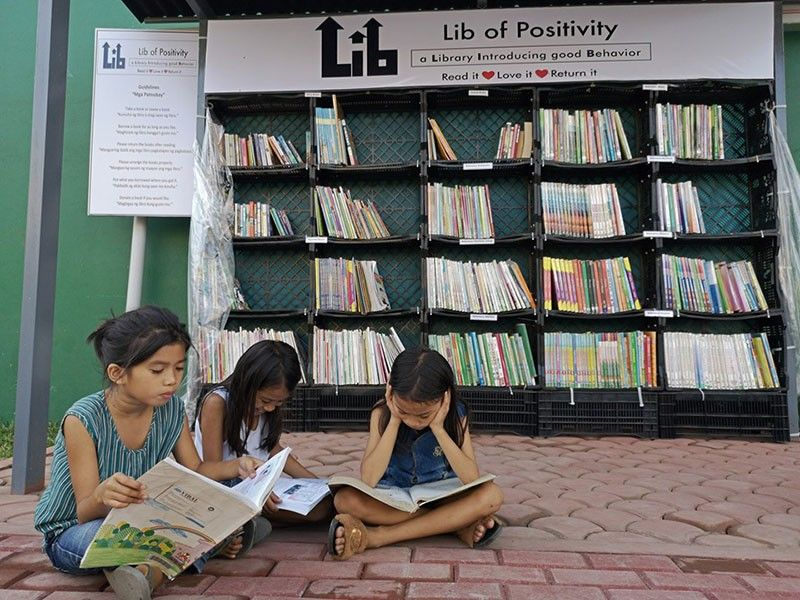 DAVAO. Library of positivity. Three young girls spend their afternoon reading history and Mapeh books at a 24/7 free library at the side of the road along Bolcan Street, Agdao, Davao City. 15-year-old Enzo Puentespina, the brainchild of the library, shares his books to encourage the youth to read, learn, and meet new friends. (Macky Lim)