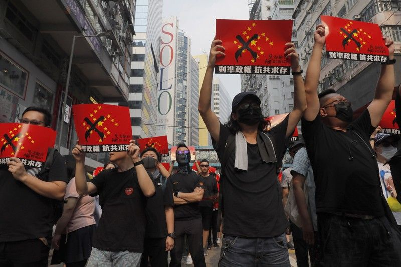 HONG KONG. Protesters march holding signs which reads