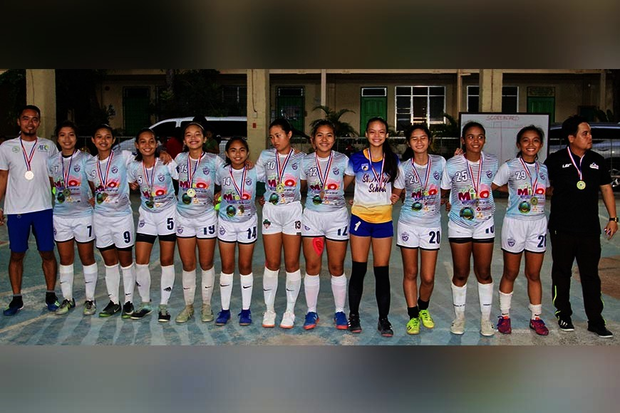 CAGAYAN DE ORO. Triumphant SMS girls' futsal team with coach Paul Cabio (right) and Jeremy Jablo. (Supplied Photo)