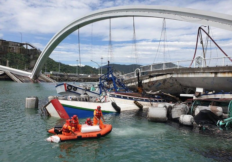 TAIWAN. Rescuers work near the site of a collapsed bridge in Nanfangao, eastern Taiwan. Tuesday, October 1, 2019. A towering bridge over a bay in eastern Taiwan has collapsed sending an oil tanker truck falling onto boats in the water below. A disaster relief official said the collapse set off a fire and at least 10 people have been hurt. (AP)