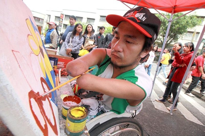 BAGUIO. Quadriplegic artist Alex Musni wows the crowed at Session road where local artists were given the spotlight to showcase their arts and crafts such as tattoos, painting and sketching on Sunday, September 29, 2019. (Jean Nicole Cortes)