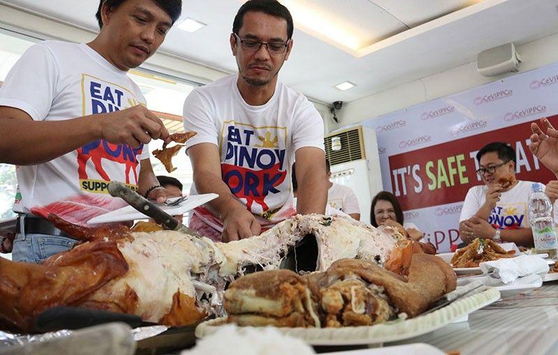 """KOOPERATIBA: Mga miyembro sa Central Visayas Pork Producer Cooperative (CeViPPCo) ningpakita sa ilang pagkaon sa lamiang litson samtang nagsul-ob og puting t-shirt nga dunay mensahe nga """"EAT PINOY PORK"""" atol sa usa ka press conference sa Chobichobi restaurant, Mabolo, Cebu City dili pa lang dugay. (SunStar File Photo)"""