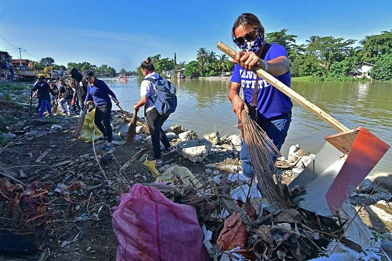 DAVAO. Staff of Davao City First District Representative Paolo Duterte spearhead the clean-up drive in Purok 7, Barangay 1-A in Davao City as part of their anti-dengue campaign. (Macky Lim)