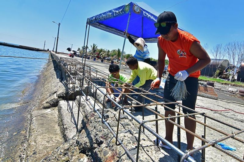 DAVAO. Gisugdan og ayo sa mga trabahante ang nadaut nga seawall sa Sta. Ana Pier sa Davao City human naguba sa kusog nga mga balud dala sa hangin nga habagat pipila ka semana na ang nakalabay. (Macky Lim)