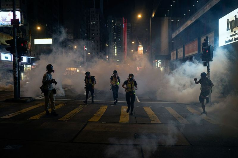 HONG KONG. Emergency responders and journalists run from tear gas during a protest in Hong Kong on Friday, October 4, 2019. Masked protesters streamed into Hong Kong streets Friday after the city's embattled leader invoked rarely used emergency powers to ban masks at rallies in a hardening of the government's stance after four months of anti-government demonstrations. (AP)